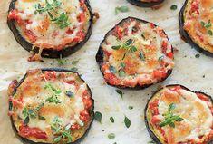 Skiver af aubergine pyntet med cherrytomater, hvidløg, basilikum og revet ost – lækre hapsere til frokost, forret eller som appetizer.