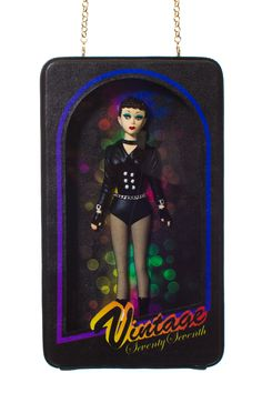 """77TH VINTAGE MADONNA BAG Black purse with Madonna inspired doll enclosed and 14k gold plated chain. 100% Polyester resin doll 100% acrylic box. SIZE & FIT 5.5""""w x 9.25""""h x 2"""" w with 24"""" chain strap 77TH 77th is a Singapore-based streetwear label known for its playful novelty clothing, jewelry and accessories."""