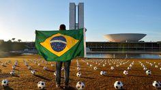 594 bolas de futebol pintadas com cruzes vermelhas foram colocadas sobre o gramado da Esplanada dos Ministérios, em Brasília, representando o número de parlamentares e o luto pela atuação do Congresso Nacional, em protesto realizado pela ONG Rio de Paz, na quarta-feira (26)