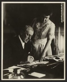 Woodrow Wilson's first posed photograph, taken in June 1920, after his stroke in September 1919. He was paralyzed on his left side, so his wife Edith holds a document steady while he signs. During his convalescence in the White House, Edith Wilson strictly limited access to her husband, misled the public on the severity of his condition and reportedly made key decisions in his name. Image: Library of Congress