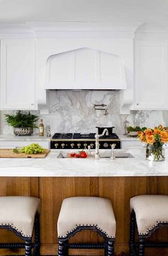 Gorgeous two-tone kitchen design with white shaker perimeter cabinets paired with calcutta marble countertops and backsplash.