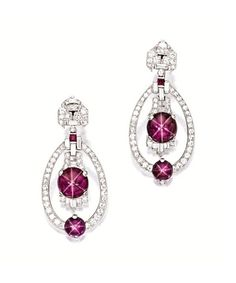 PAIR OF STAR RUBY AND DIAMOND PENDENT EARRINGS, YARD, CIRCA 1930 Of Art Deco design, each suspending an oscillating cabochon star ruby altogether weighing approximately 6.89 carats, within a frame set with baguette and circular-cut diamonds, highlighted by a similar cabochon star ruby altogether weighing approximately 3.00 carats, to a surmount set with circular-cut, baguette and half moon-shaped diamonds, the diamonds altogether weighing approximately 1.80 carats, mounted in platinum…