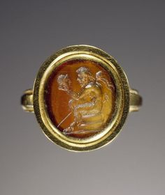 Carnelian gem set into a modern gold ring. Date: gem 1st century; ring modern. Gem engraved with the image of Pan, who sits on a round object (perhaps a rock or altar) with a beribboned thyrsos resting against his right shoulder. The god contemplates the theatrical mask he holds before him. The mask is cleanshaven, and may represent either a youthful male or a female.