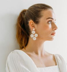 Sweet mother of pearl, in all its opalescent glory, takes center stage in the Molly Earrings. Each earring is comprised of five hand-carved mother of pearl flowers, which have been set in the center with a Swarovski crystal for added sparkle. Jewelry Model, Photo Jewelry, Clay Jewelry, Fashion Jewelry, Jewellery, Earrings Photo, Clay Earrings, Beaded Earrings, Stud Earrings