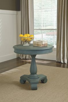 You'll be charmed by the adorable and rustic Mirimyn round accent table by Ashley Furniture. A distressed soft blue finish includes gentle rubbed-through treatment for a lovely vintage effect. Classic scrolled feet, pedestal base and turned accents complete the look.