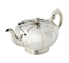 A Silver Teapot by Robert Garrard, In the form of a stylised melon with reeded sides, the finial in the shape of a seed pod. The teapot is inscribed 'From Victoria R. Christmas 1876'.  Maker's Mark: 'RG' for Robert Garrard. London, 1867 (inscription later)