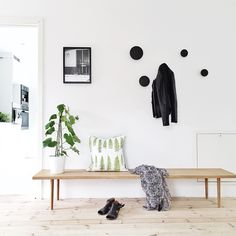 Lovely hallway with wooden bench, Muuto 'Dots' wall hooks & plant