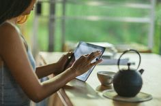 Young Asian woman sitting in her living room and using her tablet.