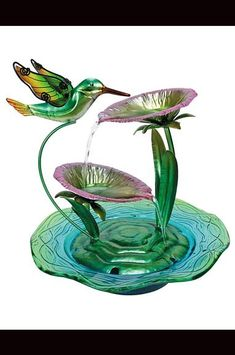 This fountain features a creative mixture of glass, metal and eye-catching color that complements the serenity offered by its blossom-to-blossom water stream. W x H x D Metal / glass Tabletop Water Fountain, Indoor Water Fountains, Indoor Fountain, Peacock Room Decor, Fountain Design, Fountain Ideas, Light Pink Flowers, Butterfly Drawing, Glass Garden