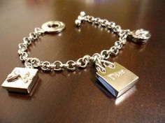 A Dior charm bracelet with a shopping bag and two gift box charms.