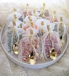 Tea: Lovely keepsakes for your tea-time guests. Twelve assorted teabag and gold-rose teaspoon tea-party favors, in embroidered ivory favor bags.