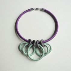 Bold circles takes unusual turns in this uniquely designed textile statement necklace. Different sized rings are adorned in ribbon colors of dark lavender, dark grey and mint green, and form a striking focal piece.  The collar measures 18 inches around and closes with a decorative silver plated end cap and a magnetic clasp for easier attachment. Total weight of this flexible, comfortable, trendy color blocked necklace is only 2 ounces.