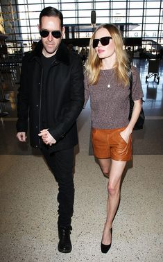 Kate Bosworth wearing a casual knit tee + tan leather shorts with Michael Polish at the airport // travel style