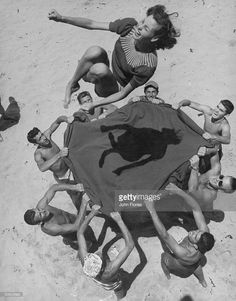 Teenaged boys using blanket to toss their friend, Norma Baker, into the air on the beach.