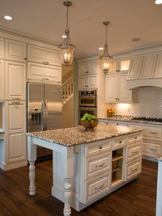 Great kitchen! Like the turned table legs on the island, the pendant lights, pantry storage around the frig, and that stove hood. Love this granite, the wood flooring and white cabinets.
