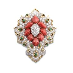 DAVID WEBB. A CORAL, EMERALD AND DIAMOND BROOCH. Designed as a central integral coral section, carved into segments, embellished to the centre with a pavé-set diamond oval, within a similarly-set surround accented with open work tear-drop motifs set with a circular-cut emerald, signed Webb, 1960s.