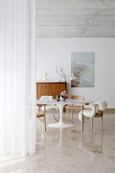 Studio space, white chairs, round table, curtains, painting, flowers, wooden drawer, lamps
