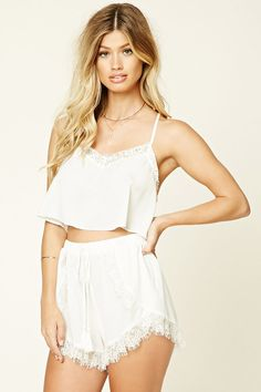 A set featuring a satin cami crop top with a buttoned racerback, adjustable spaghetti straps, lace trim, V-neckline, and wrap shorts with an elasticized waist. This is an independent brand and not a Forever 21 branded item.