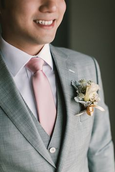 Groom in grey suit and pink tie with white and blue boutonniere // We saw and loved Andy and En-Li rustic Hong Kong ceremony, and today we're taking you inside their church wedding and dinner reception at Hilton Kuala Lumpur. Shot by Munkeat Photography, styled by Wishing Tree and planned by MY Wedding Planner, their wedding incorporated touches of rose gold with blush tones. En-Li looked beautiful in a custom-made gown by Wedding Isle and an embellished evening number by GALA by Galia…