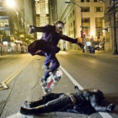 Heath Ledger skateboarding over Christian Bale during a break in filming on the set of the Dark Knight