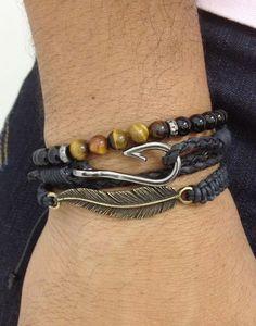 Kit unissex com 3 pulseiras sendo: - 1 pulseira com couro trançado na cor preto, com 2 voltas no punho e fecho com anzol em banho grafite. - 1 pulseira de pedra ônix contendo detalhe com pedra olho de tigre. - 1 pulseira shambala com entremeio de pena em banho ouro velho > mens bracelets shamballas onyx tiger eyer: