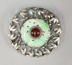 An Arts and Crafts cornelian and jade circle brooch, a circular cabochon cornelian rub set to the centre, with a twisted wire border.  A pierced and carved jade bi set to a looped silver wire frame with applied snowdrops and silver beads, unsigned, but with many similarities to the work of Mary Gage