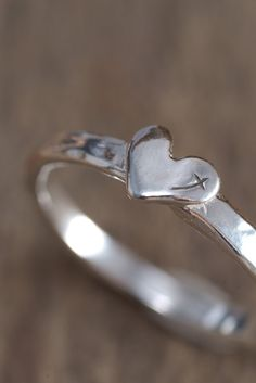 Narrow sterling silver band with raised petite heart and tiny etched cross reflection. Available in sizes: 5, 6, 7, 8, 9, 10...