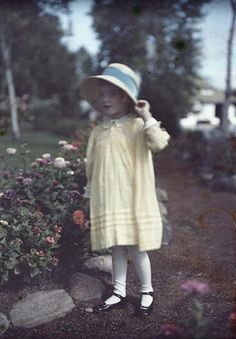 A little girl in a garden: yellow dress, bonnet with blue ribbon, stockings and mary jane flats.  Epitomises my idea of a little girl (albeit old-fashioned) || Shoes