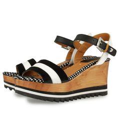 Sandalias de piel con cuña de madera de 8,5 cm, en blanco y negro. Cierre de tira para atar al tobillo con hebilla. Suela de madera y goma eva con efecto dentado.  Comodidad y estilo para todas.