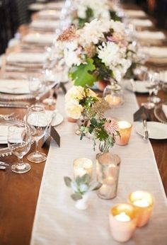 The head table will feature a large mason jar holding the bridal bouquet flanked by mason jars filled with cream hydrangeas, blush pink spray roses, fresh lavender, white scabiosa, and seeded eucalyptus, pale blue vintage candle stands topped with large mercury glass votive holders and mercury glass votives.