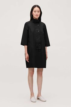Inspired by raincoat details, this dress is made from crisp cotton with a lightweight feel. Shaped for a voluminous fit that widens at the middle, it has a stand collar, dropped shoulders and a front fastening with a wide placket. Large Buttons, New Dress, Knitwear, Raincoat, Women Wear, High Neck Dress, Man Shop, Style Inspiration, How To Wear