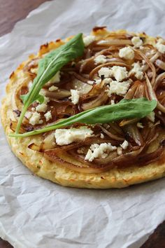 Receita de pizza de couve-flor com cebola caramelizada, e ainda queijo esfarelado e folhas de rúcula. Uma receita sem glúten e vegetariana.