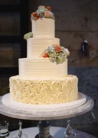 Four tiered vintage inspired buttercream cake with rosette and floral accents