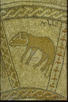 """Aries depicted by a lamb in profile with a long tail, facing left; inscribed in Hebrew in the upper right corner: טלא """"Aries"""" The panel is framed at top & bottom by guilloche bands, on the right by a row of flower buds, and on the left by a band of opposite stepped triangles from Beth Alpha Synagogue. Artist/ Maker: Marianus and his son Hanina (Artisan). Date: 518-527, Justin I, or 567-578, Justin II. Period: Byzantine. Origin: Israel/Eretz Israel 