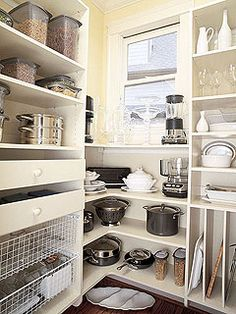 The butler's pantry has tall shelves that hold large pots and pans.