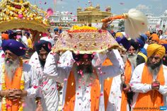 INDIA, Amritsar : An Indian Sikh priest ® carries the Sikh holy book during a procession from the Sri Akal Takhat at the Sikh Shrine to the  Golden Temple in Amritsar on April 8, 2015 on the eve of the 394th birth  anniversary of the ninth Sikh Guru, Teg Bahadur. Guru Tegh Bahadur, the  youngest of five sons of Guru Hargobind, was born in Amritsar in 1621  and was executed on the orders of Mughal Emperor Aurangzeb in Delhi in  1675. AFP PHOTO/ NARINDER NANU