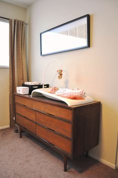 This Mid Century Dresser Is Being Used As A Changing Table For A Very Young  Woman