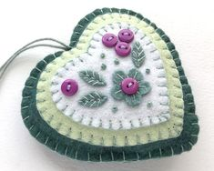 A handmade felt heart ornament in fresh Spring colours, with embroidered leaves and purple blossom made from little buttons. The heart ornament measures 10 cm/ 4 inches across and has a loop for hanging. Its also available with yellow blossoms here; Felt Christmas Decorations, Felt Christmas Ornaments, Christmas Crafts, Diy Ornaments, Christmas Nativity, Beaded Ornaments, Christmas Printables, Homemade Christmas, Christmas Christmas