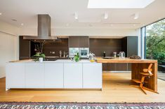 A modern galley kitchen with light wood floor and dark wood cabinets. What I like here is the wooden kitchen table attached to the island.