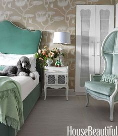 "Lolly, the family poodle, lounges in the Dorothy Draper-influenced master bedroom. Galli chose the overscale Cole & Son wallpaper, Lily, for ""the fairy-tale feeling."" The lily pads and the Old World Weavers green velvet, Languedoc, on the headboard evoke the romance of a garden pond. The French Canopy chair from Artistic Frame is covered in Beacon Hill's In Between."