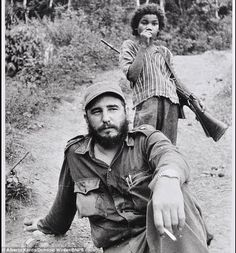 Fidel Castro with a child guardian armed with a rifle in the Cuban jungle....what kind of man hides behind a child?