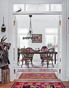 Boho dining room with ethnic rugs bamboo chairs, white walls, eclectic