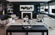 haus interior living room with black lacquer wall paint, chevron pillows and upholstered lounge chairs, white sofas, fireplace with modern art hanging on the wall above it