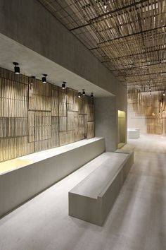 Woven bamboo screens are suspended from the ceiling to form a hanging installation that resembles a chandelier, others cover the walls in the corners of the store, spanning all the way down to the floor.