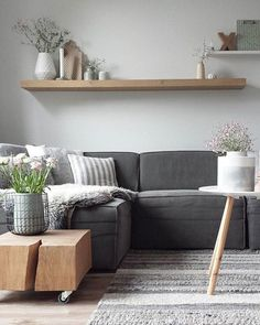 This shows the combination of different shades of cold gray and wood in natural color which gives the room warmth. Plants give life to the room, because of them room breath. No unnecessary things, little but enough for a comfortable and happy life.