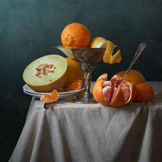 Citrus Fruit And Melon - Fruit classic still life photography with fresh citrus fruit, grapefruit, orange, lemon and melon in vintage vase on drapery and on light blue background  by Nikolay Panov - https://pixels.com/products/citrus-fruit-and-melon-nikolay-panov-art-print.html