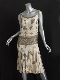 French beaded satin flapper dress, circa 1925. The hip band and border panels are of gold lamé. The design glitters with a mix of rhinestones, crystal beads, and silver lined glass beads.