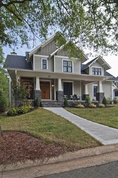 The front facade of this home features three front gables and a Sherwin-Williams color scheme, with the siding in Chatroom 6171, the board and batten accents in Hardware 6172 and the trim and fascia board in Dover White 6385.