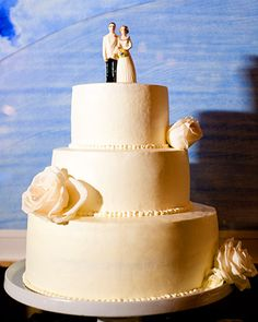 Simple white cake decorated with white roses and a classic bride and groom cake topper
