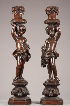 A pair of French sculpted walnut figures of Putti standing on swag carved plinths supporting associated baskets of fruit. Late 17th century...
